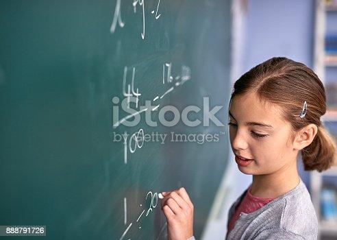 Cropped shot of an elementary school girl writing on a blackboard in class
