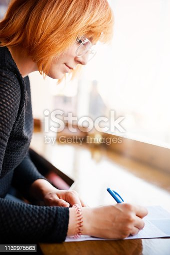 Cropped shot of a young woman doing paperwork in a cafe