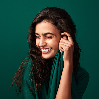 Shot of a beautiful young woman posing against a green background