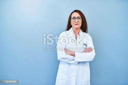 Studio portrait of a mature scientist standing against a blue background