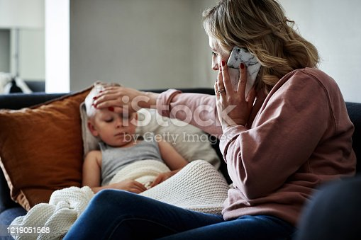 Shot of a mother wearing a surgical mask making a phone call while aiding to her sick young son at home