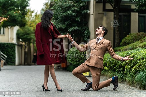 Young good-looking man kneeling on his knee outdoor, holding hand of his beautiful girlfriend