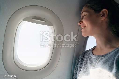Young woman looking through the airplane window.