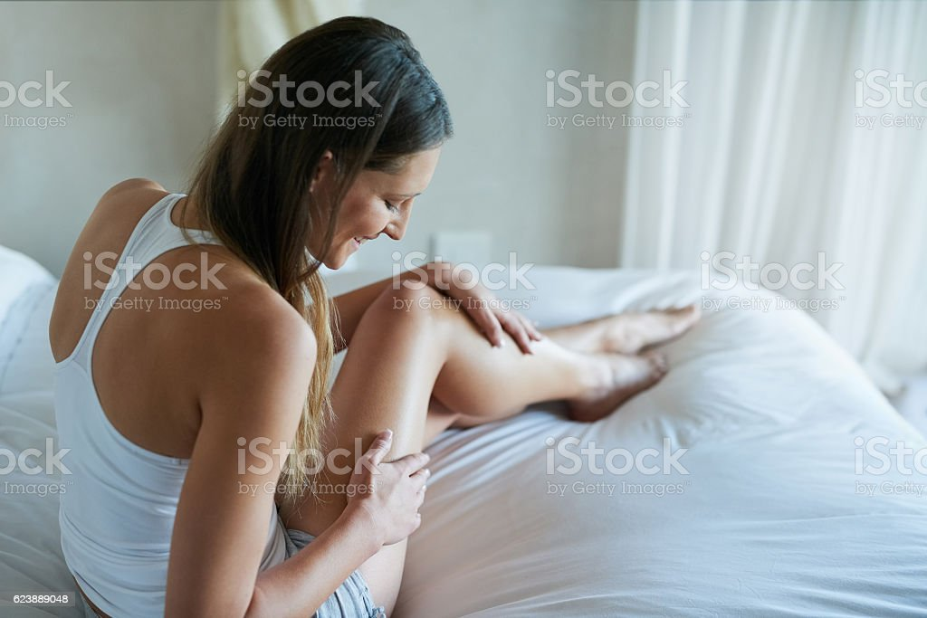 She's feeling beautiful in her own skin Shot of a happy young woman stroking her thigh while sitting on her bed 20-29 Years Stock Photo