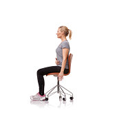 Profile of a beautiful young woman sitting upright in a chair and correcting her posture against a white background