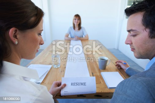 A pretty young woman sitting at the end of the table as two businesspeople go over her long resume