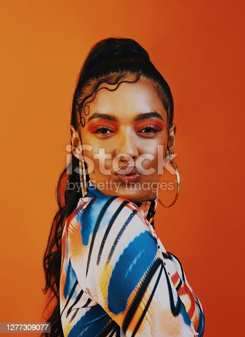 Shot of a young woman posing against a orange background with a trendy hairstyle