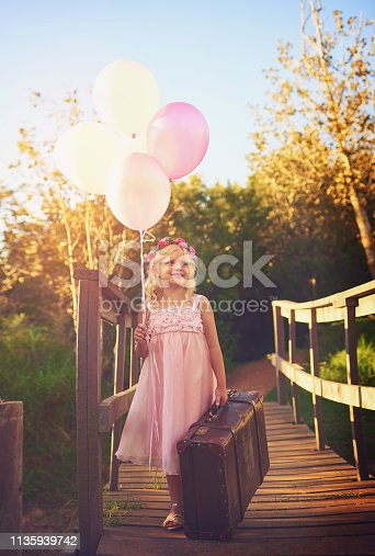 Shot of a happy little girl holding balloons and a suitcase while standing in the middle of a bridge