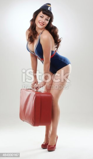 Full length of a glamorous nautical pin up girl with her suitcase