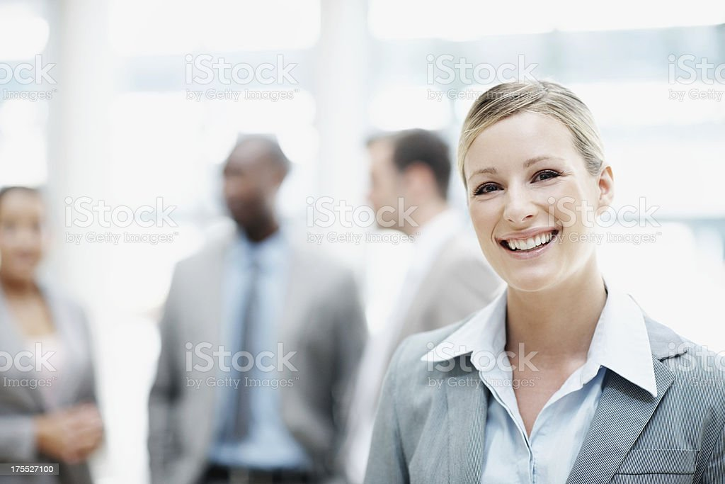 She's going to be a CEO one day Smiling young businesswoman looking at the camera with her colleagues in the background Adult Stock Photo