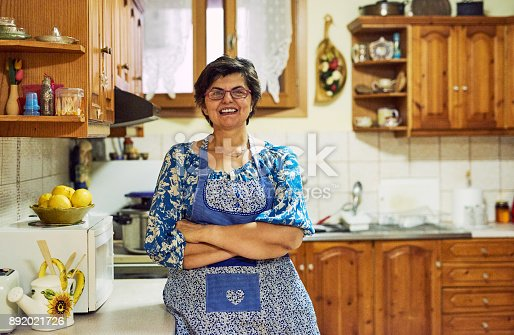 Portrait of a cheerful mature woman standing with arms folded while looking into the camera in the kitchen at home