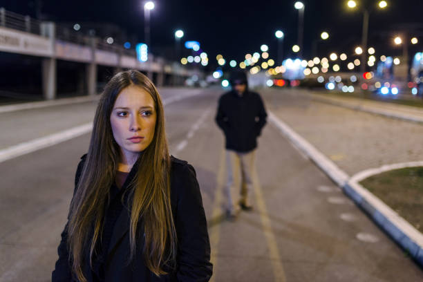 She's got a bad feeling Beautiful young woman walking and being stalked by man criminal on the street at night. Dangerous situation for lonely female. Unrecognizable male figure with hidden face in hood walking, looking dangerous, stalking night robber burglar, bad troubled period, hooded guy Following frightened woman harassment stock pictures, royalty-free photos & images