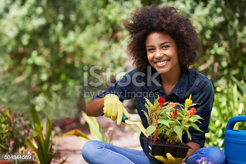 Portrait of a happy young woman doing some gardening