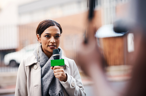 Shot of an attractive young news reporter covering a story outdoors in the city