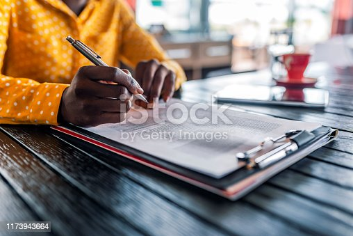 Close-up Of Businesswoman's Hand Signing On Papers Over Desk while sitting during the day. Filling out an important form. American woman working at home. Focus on hand. Close up.