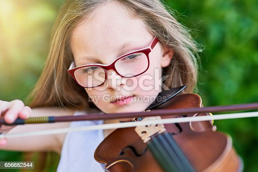 Cropped shot of a little girl playing the violin outside