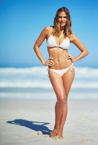 She's got reason to be confident this summer Full length portrait of a sexy young woman standing with her hands on her hips at the beach bikini stock pictures, royalty-free photos & images