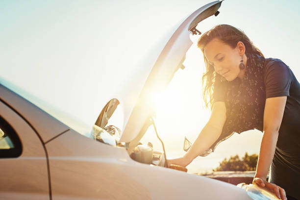 She's got some mechanical difficulties with her car Cropped shot of a young woman checking under the hood of her car after breaking down on the roadside vehicle hood stock pictures, royalty-free photos & images