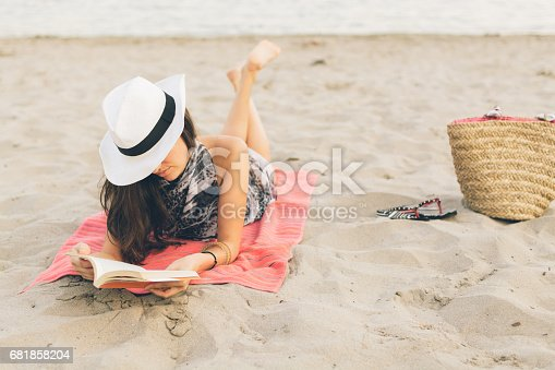 Front view image of an attractive young female in swimwear with sunhat. She is lying on beach towel and reading a book. Beach bag and flip flops aside