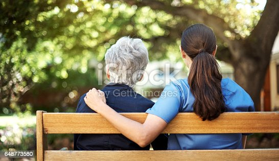 Rearview shot of a senior woman sitting with a nurse on a bench out in the garden