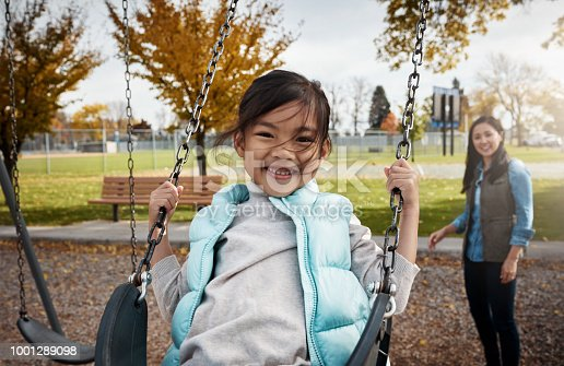 Portrait of a little girl playing on a swing at the park with her mother in the background