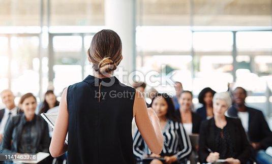 Shot of a young businesswoman delivering a speech during a conference