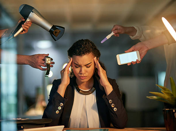She's got too many demands and distractions to deal with Cropped shot of a stressed out businesswoman working late in an office distractions stock pictures, royalty-free photos & images