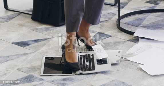 Cropped shot of an unrecognizable businesswoman breaking a laptop by jumping on it in an office