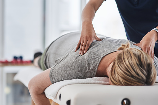 Shot of a mature woman lying face down and getting her back massaged by a physiotherapist at a clinic