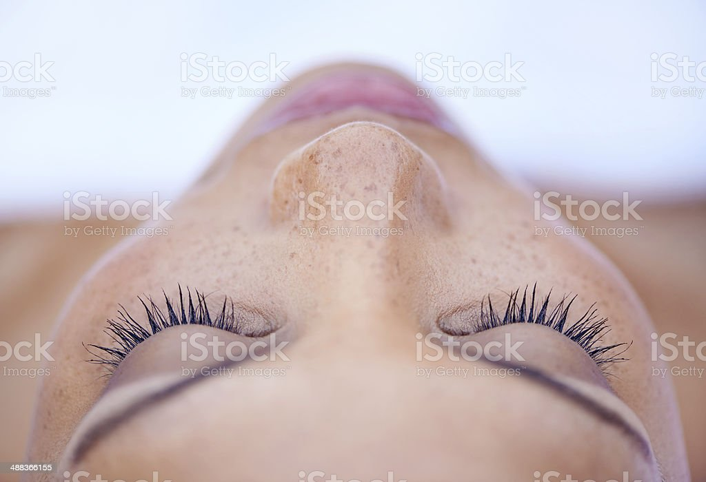 She's in a deeply relaxed state of mind Cropped shot of an attractive young woman lying on her back 20-29 Years Stock Photo