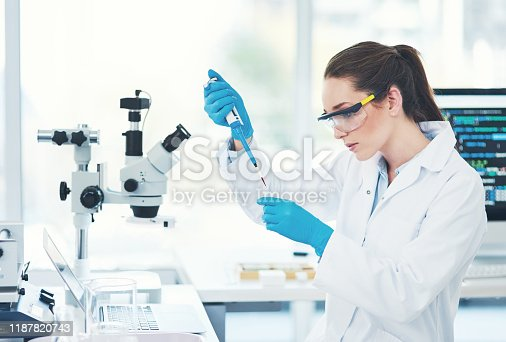 Cropped shot of a focused young female scientist wearing protective glasses while pouring a test sample into a vile inside of a laboratory