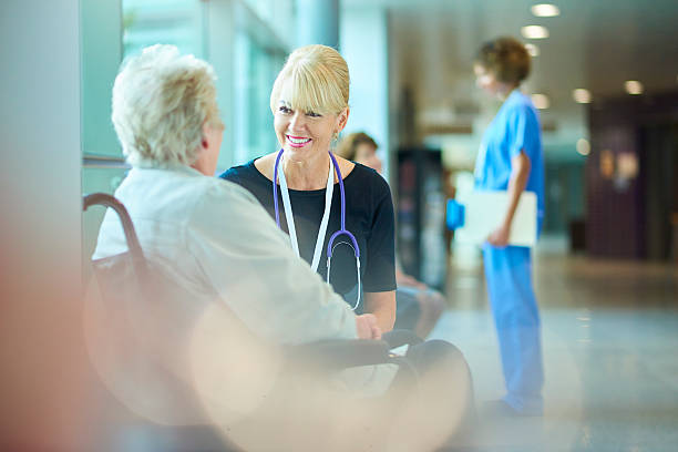 she's in good hands an elderly hospital patient sits in a wheelchair in the corridor of a hospital chatting to a senior doctor sitting next to her . In the background a nurse is chatting to another patient . outpatient stock pictures, royalty-free photos & images
