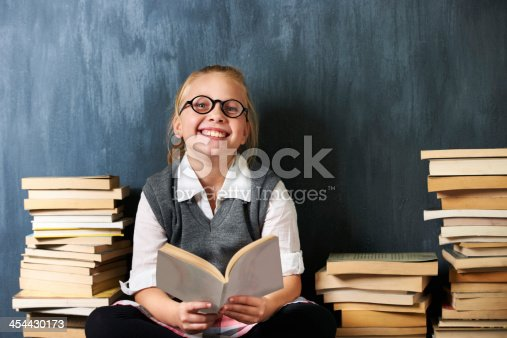A happy blonde girl reading in class surrounded by books