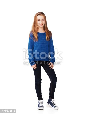 Full body portrait of a pretty young girl standing against a white background