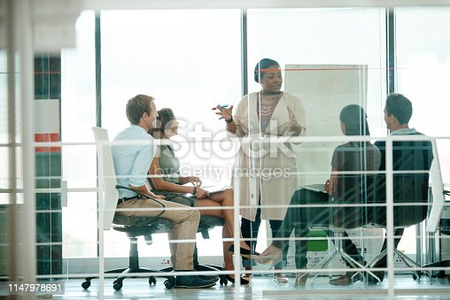 Full length shot of a businesswoman giving a presentation during a meeting in the boardroom