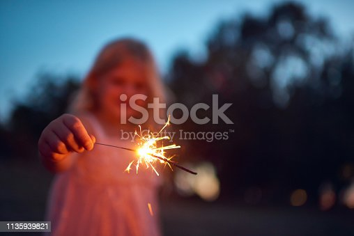 Shot of an unrecognizable little girl playing with a sparkler at night time outside in nature