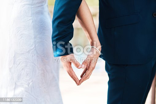 Cropped shot of an unrecognizable newlywed couple making a heart shape with their hands while standing outdoors on their wedding day