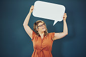 Studio shot of a woman holding a speech bubble against a blue background
