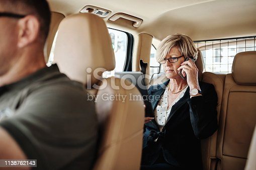 Shot of a mature businessman talking on a cellphone while being driven in the backseat of a car