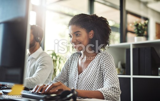 Shot of a young businesswoman working on her computer with her colleague in the background