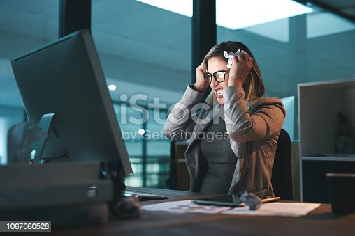 Shot of a young businesswoman looking frustrated while working late in an office