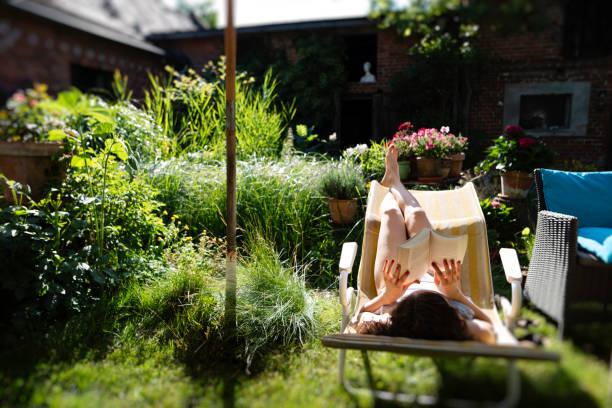 sie ist ein buch im garten lesen. - sonnenschirm terrasse stock-fotos und bilder