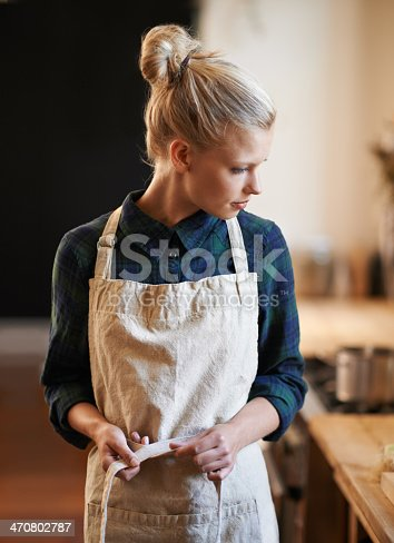 An attractive young woman  wearing an apron