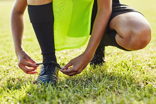 Cropped shot of an unrecognizable female soccer player lacing up her boots outdoors on the field