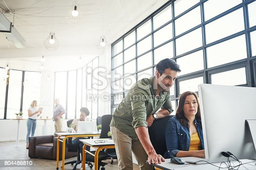Shot of a male designer assisting his colleague at her desk