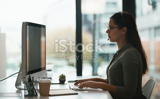 Shot of a young call centre agent working on a computer in an office