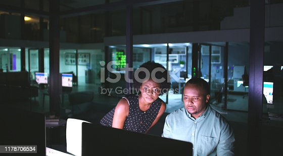 Shot of two businesspeople working late at the office