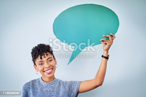 Portrait of an attractive young woman holding up a speech bubble against a blue background