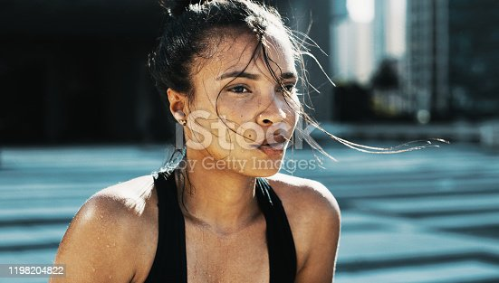 Shot of a sporty young woman catching her breath while exercising in the city
