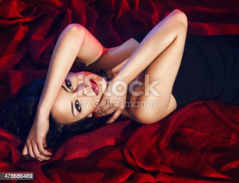 Cropped portrait of a desirable young woman posing on a bed with a red velvety covering